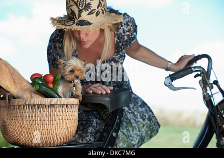 Mature woman on electric bike with dog and vegetables in basket - Stock Photo
