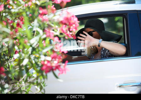 Mature woman driving car, wearing disguise and hiding face with hand - Stock Photo