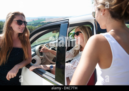 Mature woman sitting in car, talking to teenagers - Stock Photo