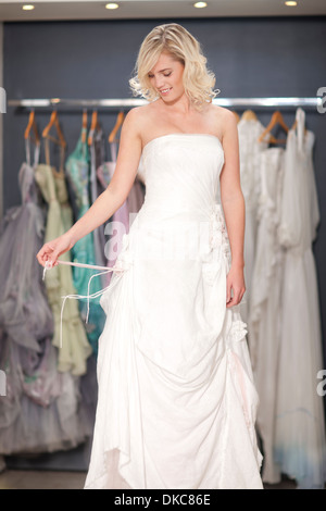 Young woman trying on wedding dress - Stock Photo
