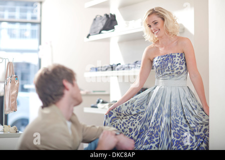 Young woman trying on dress - Stock Photo