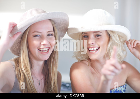 Young women trying on hats - Stock Photo