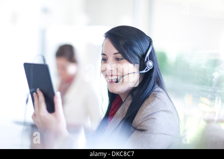 Businesswoman using digital tablet and having telephone conversation on headset - Stock Photo