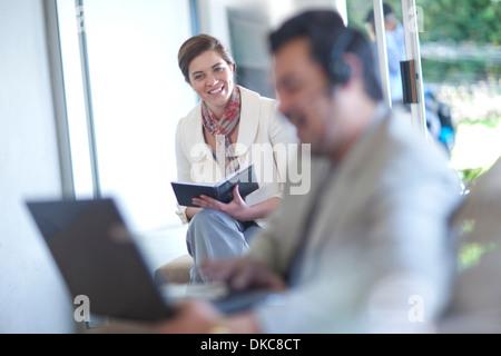 Businessman using laptop, businesswoman writing - Stock Photo
