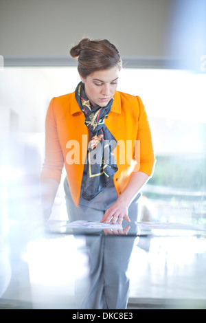 Businesswoman looking at paperwork on desk - Stock Photo