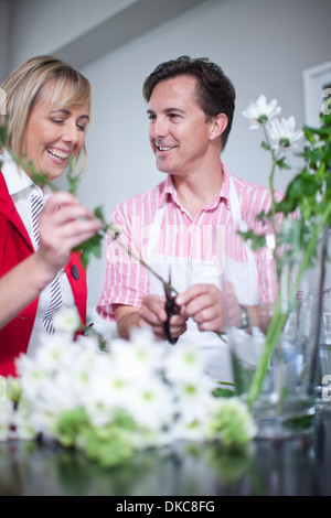 Mature couple arranging flowers in vase - Stock Photo