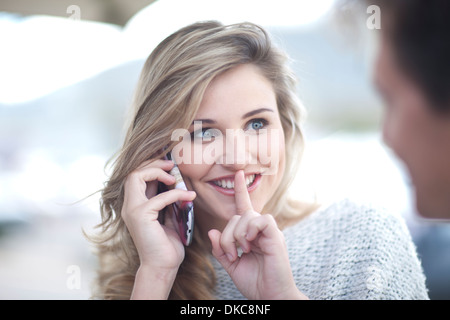 Young woman on phonecall with finger to lips - Stock Photo