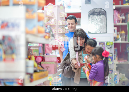 Family with two daughters shopping in toy shop - Stock Photo