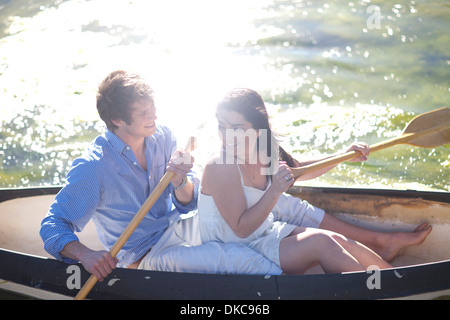Young couple in rowing boat on river in sunlight - Stock Photo