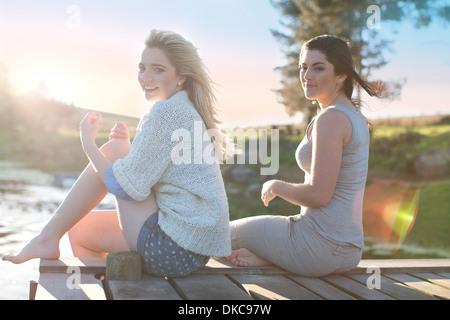 Two female friends sitting on breezy pier - Stock Photo