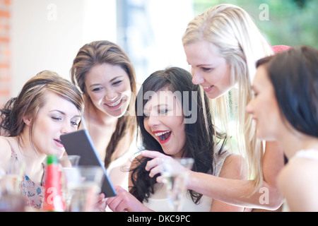 Female friends laughing at digital tablet - Stock Photo