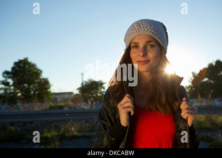 Portrait of young woman in leather jacket and beanie - Stock Photo