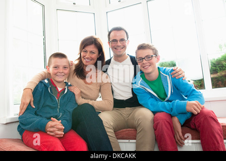 Family portrait in front of window - Stock Photo