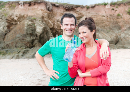 Portrait of couple on beach with water bottle - Stock Photo
