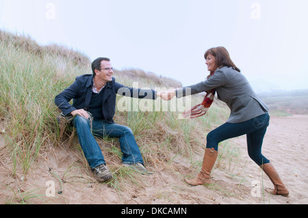 Couple getting up from sand dune - Stock Photo