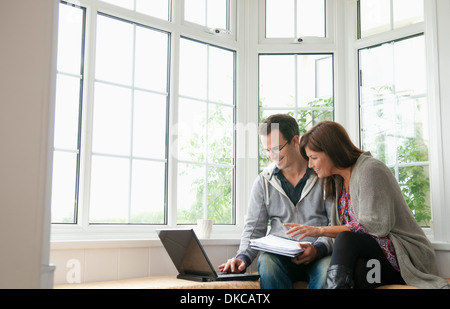 Couple on window seat, using laptop - Stock Photo