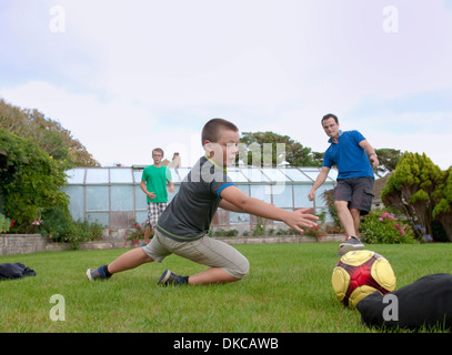 Father and sons playing football in garden - Stock Photo