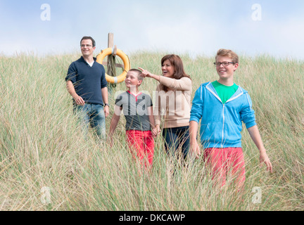 Family strolling in sand dunes - Stock Photo