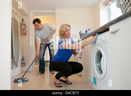 Mid adult couple cleaning kitchen in new home - Stock Photo