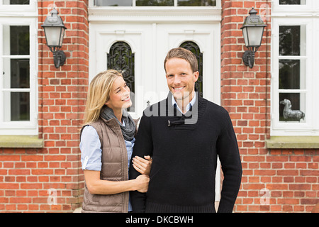 Mid adult couple outside house - Stock Photo