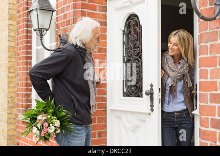 Senior man with bouquet, mid adult woman opening front door - Stock Photo