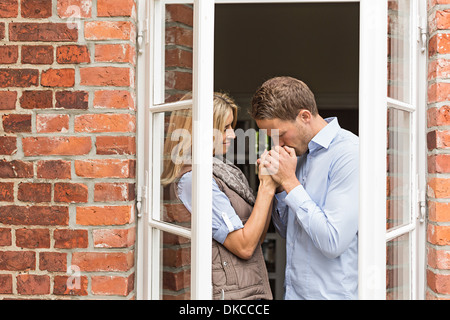 Mid adult couple by window, man kissing woman's hands - Stock Photo