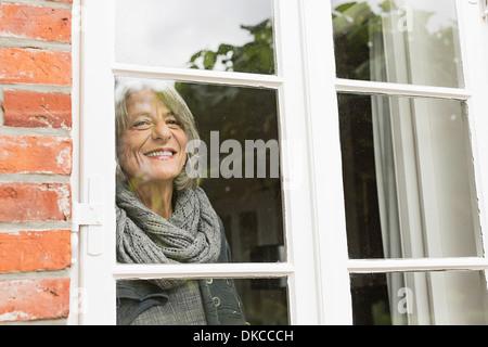 Senior woman looking through window - Stock Photo