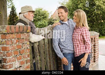 Senior man leaning on gate talking to with mid adult couple - Stock Photo