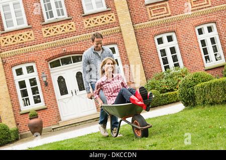Mid adult man pushing woman in wheelbarrow