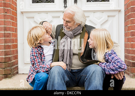 Grandfather sitting with grandchildren on front doorstep - Stock Photo