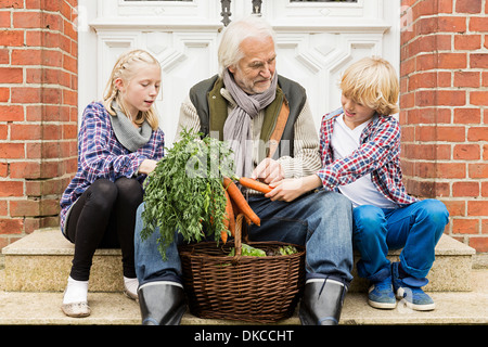 Grandfather sitting with grandchildren on doorstep with carrots - Stock Photo