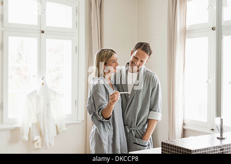 Mid adult couple, woman holding pregnancy test - Stock Photo