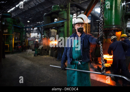 Operative prepares to hook steel billet out of furnace. Team in background using counterblow hammer - Stock Photo