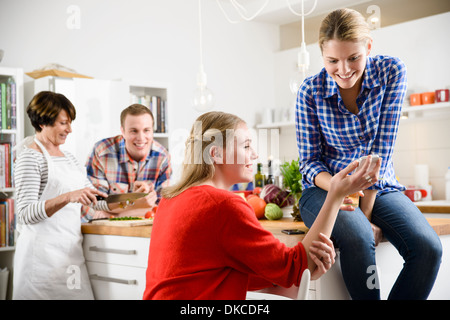 Two women with cell phone in kitchen, mother and brother in background - Stock Photo