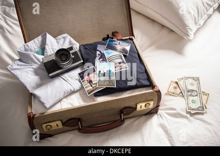 Open suitcase on bed with camera and photographs - Stock Photo