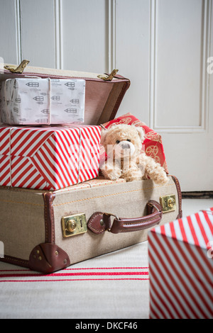 Suitcase filled with wrapped gifts and teddy bear - Stock Photo