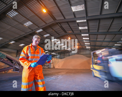 Worker checking clipboard in warehouse with zircon sand as forklift truck passes - Stock Photo