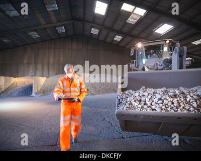 Worker checking clipboard in mineral store passing digger full of metal alloy - Stock Photo