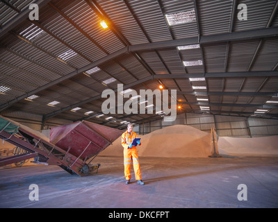 Worker checking clipboard in warehouse with zircon sand - Stock Photo