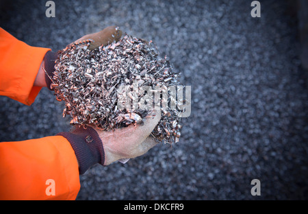 Close up of worker holding titanium turnings - Stock Photo