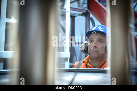 Worker in hard hat and ear defenders inspecting zircon sand - Stock Photo