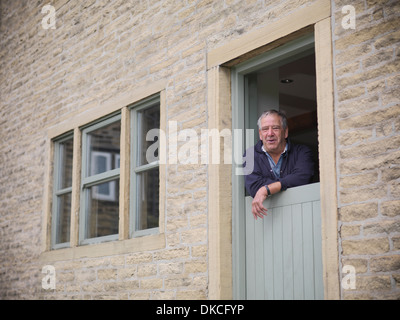 Portrait of mature farmer looking out from farmhouse door - Stock Photo
