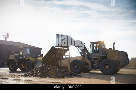 Dumper trucks sorting and organising pig iron in industrial works - Stock Photo