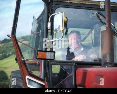 Mature farmer in tractor cab, portrait - Stock Photo