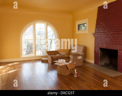 An empty room in a residential house and cardboard boxes suggesting someone is moving in or out. - Stock Photo