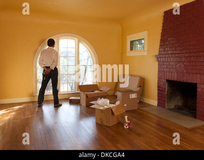 A man looks out of an empty room in a residential house and cardboard boxes suggesting he is moving in or out. - Stock Photo