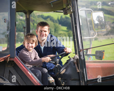 Farmer and young son in tractor in field, portrait - Stock Photo