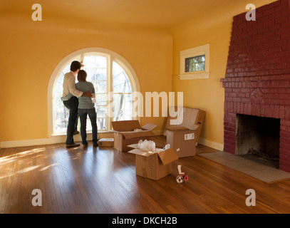 A couple in an empty room in a residential house with cardboard boxes suggesting they are moving in or out. - Stock Photo