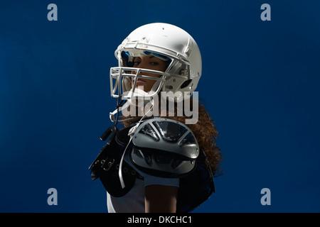 Portrait of female american footballer wearing helmet - Stock Photo