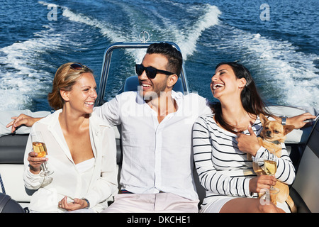 Young man on boat with arms around women, Gavle, Sweden - Stock Photo